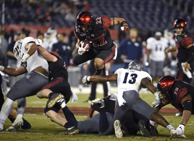 San Diego State running back Chase Jasmin (22) jumps over Nevada defensive back Jordan Lee (13) during the first half of a college football game Saturday, Nov. 9, 2019, in San Diego. U.S. (AP Photo/Denis Poroy)