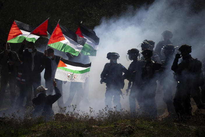 """FILE - In this Thursday, Dec. 3, 2020. file photo, Israeli border police officers and Palestinians clash during a protest against the expansion of Israeli Jewish settlements near the West Bank town of Salfit. Israel's premier human rights group has begun describing both Israel and its control of the Palestinian territories as a single """"apartheid"""" regime, using an explosive term that the Israeli government and its supporters vehemently reject. (AP Photo/Majdi Mohammed, File)"""