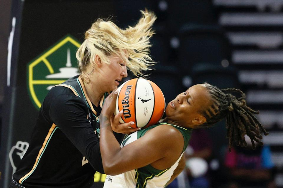 Kylee Shook and Epiphanny Prince battle for a ball during a WNBA game between the New York Liberty and Seattle Storm.