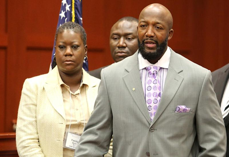 Tracy Martin, right, and Sybrina Fulton, the parents of slain teen Trayvon Martin, make a statement to reporters during a news conference at the Seminole County Courthouse, in Sanford, Fla., Wednesday, June 12, 2013. In the background is their attorney Benjamin Crump. (AP Photo/Orlando Sentinel, Joe Burbank, Pool)