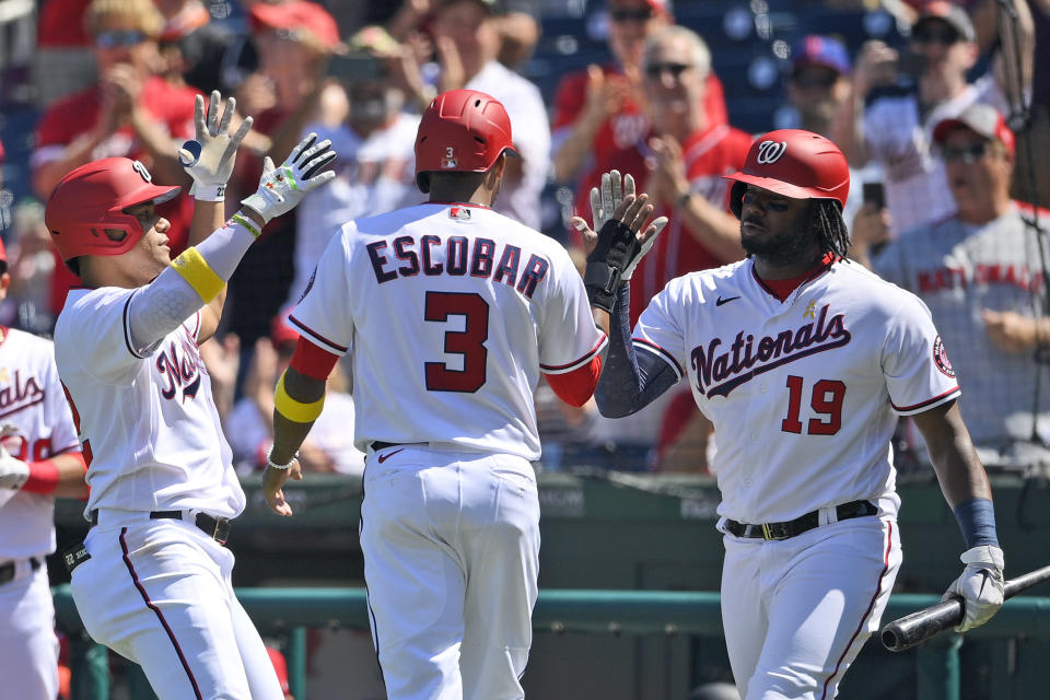 Washington Nationals' Juan Soto, left, celebrates his two-run home run with Alcides Escobar (3) and Josh Bell (19) during the third inning of a baseball game against the Philadelphia Phillies, Thursday, Sept. 2, 2021, in Washington. (AP Photo/Nick Wass)