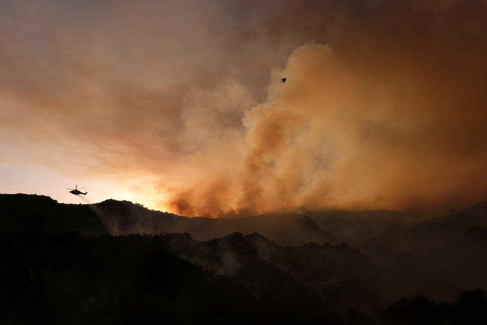 A helicopter drops water as smoke rises from a brush fire scorching at least 100 acres in the Pacific Palisades area of Los Angeles on Saturday, May 15, 2021. (AP Photo/Ringo H.W. Chiu)