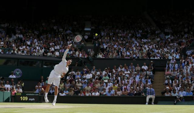 Milos Raonic of Canada serves during his men's singles semi-final tennis match against Roger Federer of Switzerland at the Wimbledon Tennis Championships, in London July 4, 2014. REUTERS/Stefan Wermuth (BRITAIN - Tags: SPORT TENNIS)