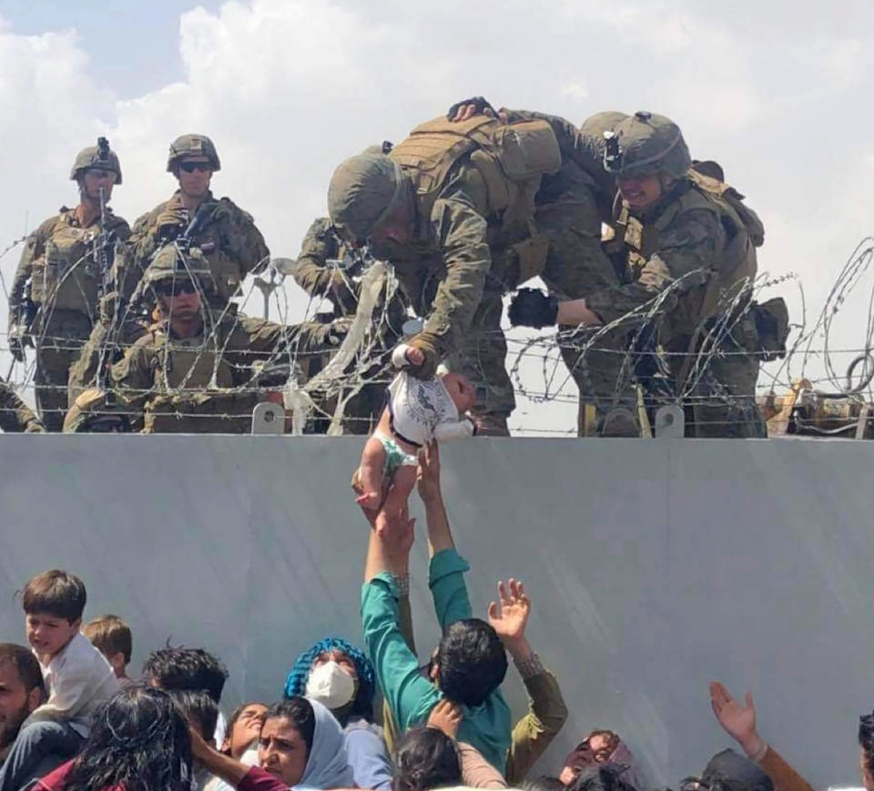 The photo of Liya being lifted across a barbed wire wall at  Kabul Airport in Afghanistan by US soldiers.