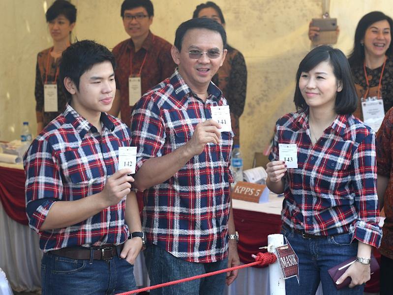 """Jakarta's Christian governor Basuki Tjahaja Purnama (C), better known as """"Ahok"""", flanked by his wife Veronica (R) and son Nicholas (L) show off their ballot papers in Jakarta on February 15, 2017 (AFP Photo/GOH CHAI HIN)"""