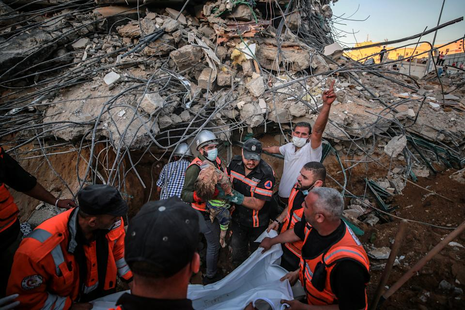Palestinian workers take part in rescue efforts to pull out a body of a child from rubble.