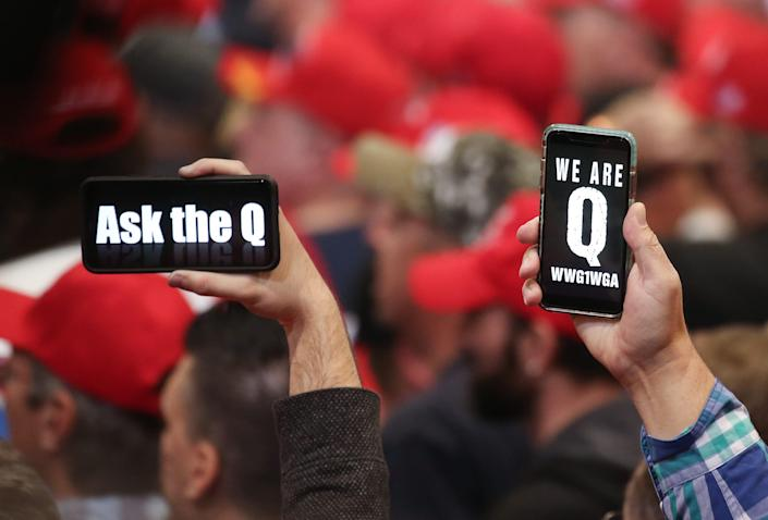 Supporters of President Donald Trump hold up their phones with messages referring to the QAnon conspiracy theory at a campaign rally at Las Vegas Convention Center on February 21, 2020 in Las Vegas, Nevada.