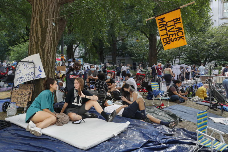 Protesters gather beneath a Black Lives Matter sign at an encampment outside City Hall, Friday, June 26, 2020, in New York. (AP Photo/John Minchillo)