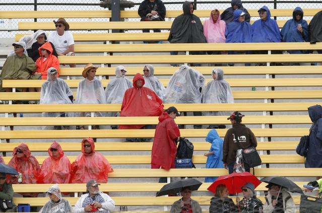 Spectators cover up as rain falls, suspending the NASCAR Nationwide auto race on Saturday, March 1, 2014, in Avondale, Ariz. (AP Photo/Ross D. Franklin)