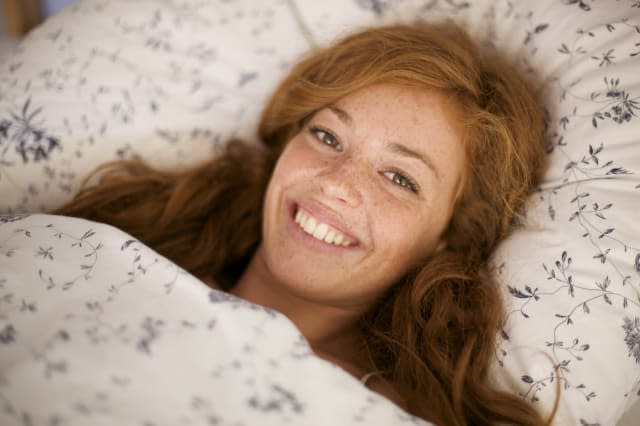 Smiling woman lying in bed
