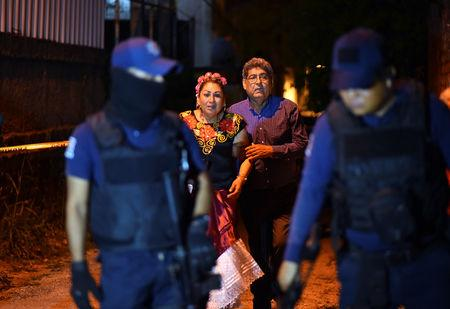 People react next to police officers guarding a crime scene where unidentified assailants opened fire at a bar in Minatitlan, in Veracruz state, Mexico, April 19, 2019. Picture taken April 19, 2019. REUTERS/Angel Hernandez