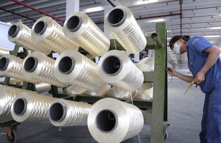 An employee works at a production line of a textile factory in Lianyungang, Jiangsu province, August 1, 2016. China Daily/via REUTERS