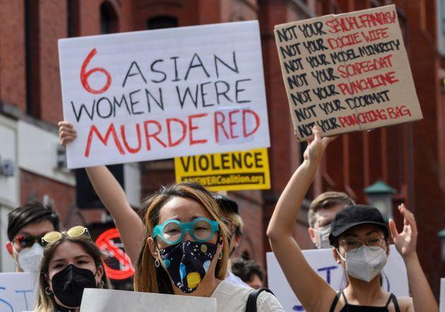 Asian women at a protest in Washington's Chinatown on March 27, 2021. One woman holds a sign that reads