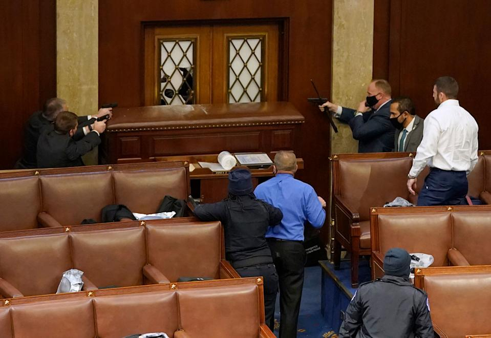 US Capitol police officers point their guns at a door that was vandalised in the House Chamber during a joint session of Congress on January 6.