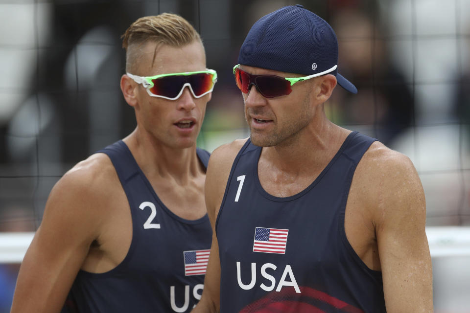 FILE - In this Aug. 16, 2016, file photo, the United States team of Casey Patterson, left, and Jacob Gibb walk on the pitch during a men's beach volleyball match against Spain at the 2016 Summer Olympics in Rio de Janeiro, Brazil. Since the spread of coronavirus, three beach volleyball events in China and Singapore have been postponed until after the Summer Games or canceled outright, and the five-star World Tour Finals is in Italy, another focus of the outbreak. (AP Photo/Petr David Josek, File)