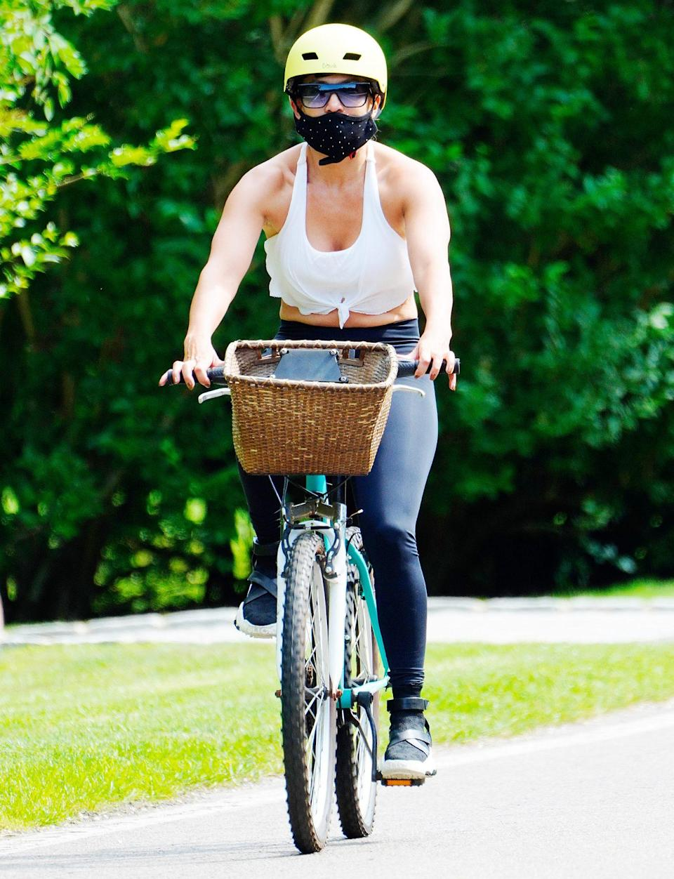 <p>Jennifer Lopez wears a face mask and helmet on a solo bike ride in The Hamptons on Thursday ahead of her 51st birthday. </p>