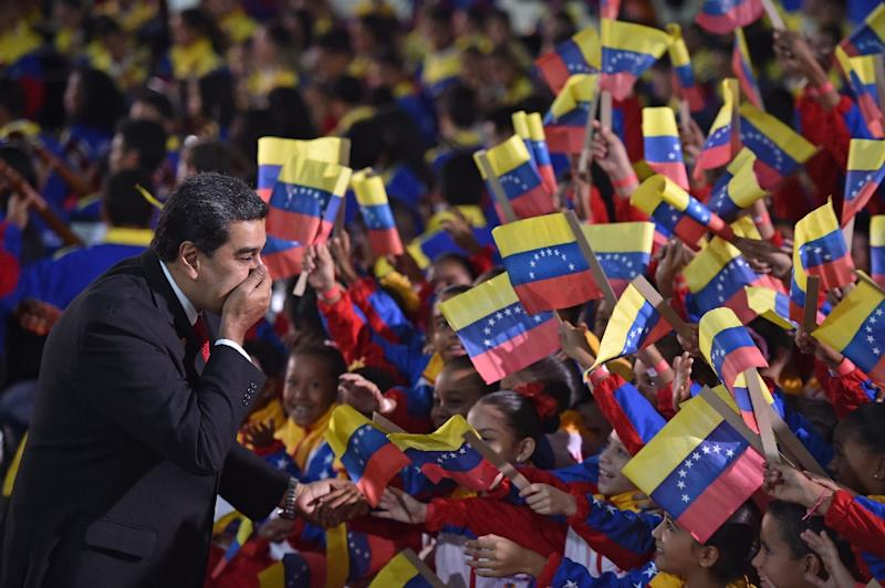 President Nicolas Maduro blows kisses at children waving the Venezuelan flag as he arrives for his inauguration (AFP Photo/YURI CORTEZ)