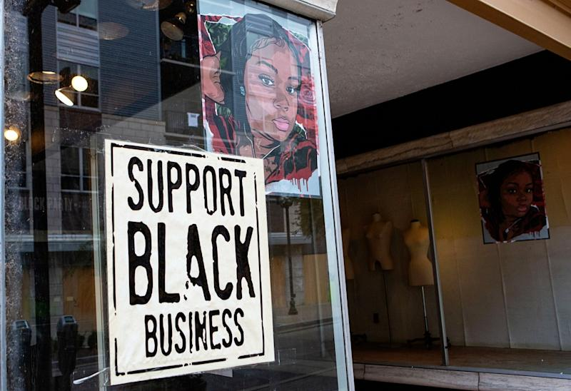 A portrait of Breonna Taylor is seen in the front window of a downtown Louisville business.