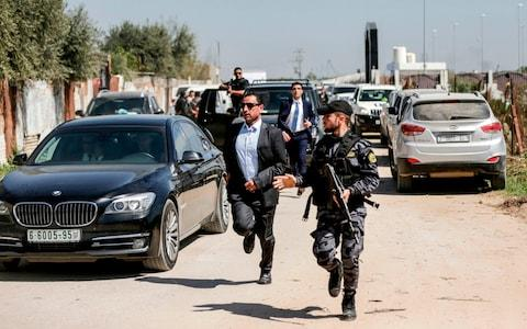 A bodyguard of the Palestinian Prime Minister (C) and a Hamas security officer (R) escort the PM's convoy as he leaves Gaza City - Credit: MAHMUD HAMS/AFP/Getty Images
