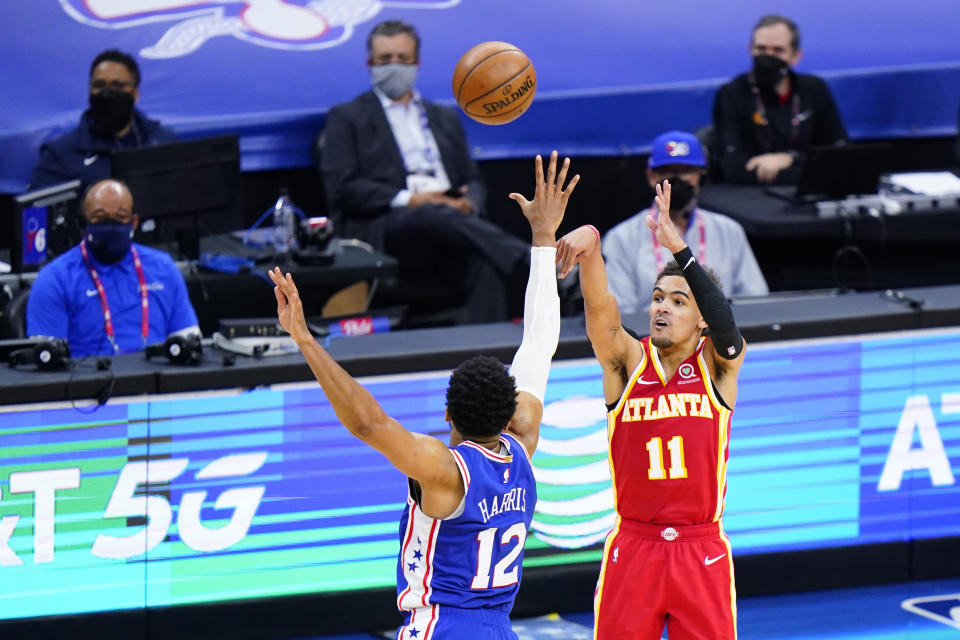 Atlanta Hawks' Trae Young, right, goes up for a shot against Philadelphia 76ers' Tobias Harris during the second half of Game 5 in a second-round NBA basketball playoff series, Wednesday, June 16, 2021, in Philadelphia. (AP Photo/Matt Slocum)
