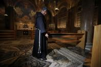 A priest inspects a damaged church floor after a man tried to set fire to the Church of All Nations next to the Garden of Gethsemane in Jerusalem