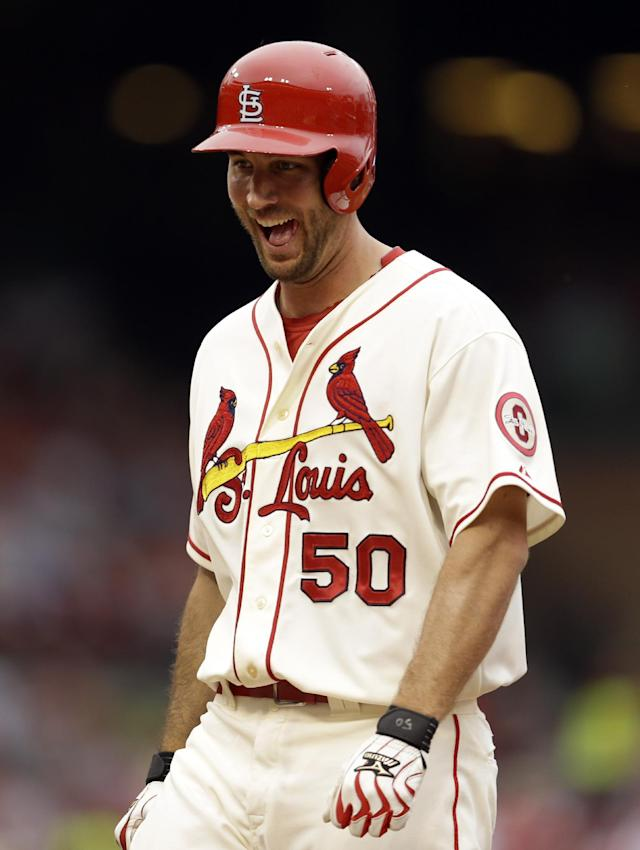 St. Louis Cardinals' Adam Wainwright laughs as he stands on first after hitting an RBI-single during the third inning of a baseball game against the Chicago Cubs, Saturday, Sept. 28, 2013, in St. Louis. (AP Photo/Jeff Roberson)