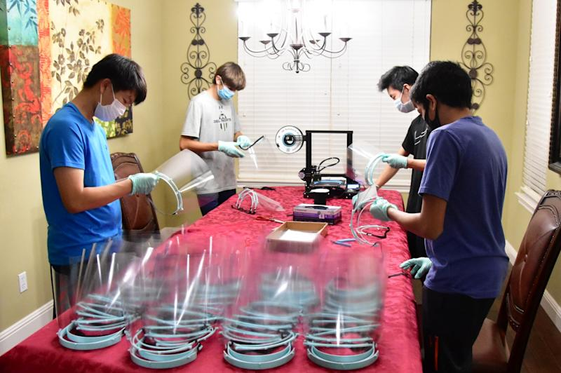 Andrew Zhang, Jerry Wu, Nick Genovese and Rishi Peddakama assembling face shields for health care workers. (Photo courtesy of Shield Our Health Heroes)