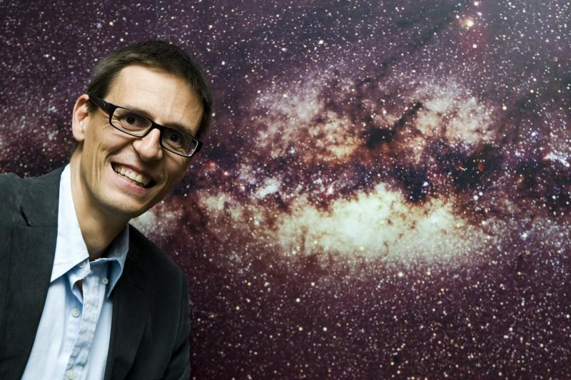 """FILE - In this Wednesday, Sept. 16, 2009 file photo Swiss astrophysicist Didier Queloz poses in front of the picture of the Milky Way at the Geneva Observatory in Geneva, Switzerland. The 2019 Nobel prize in Physics was given to James Peebles """"for theoretical discoveries in physical cosmology,"""" and the other half jointly to Michel Mayor and Didier Queloz """"for the discovery of an exoplanet orbiting a solar-type star,"""" said Prof. Goran Hansson, secretary-general of the Royal Swedish Academy of Sciences that chooses the laureates.  (Salvatore Di Nolfi, Keystone via AP)"""