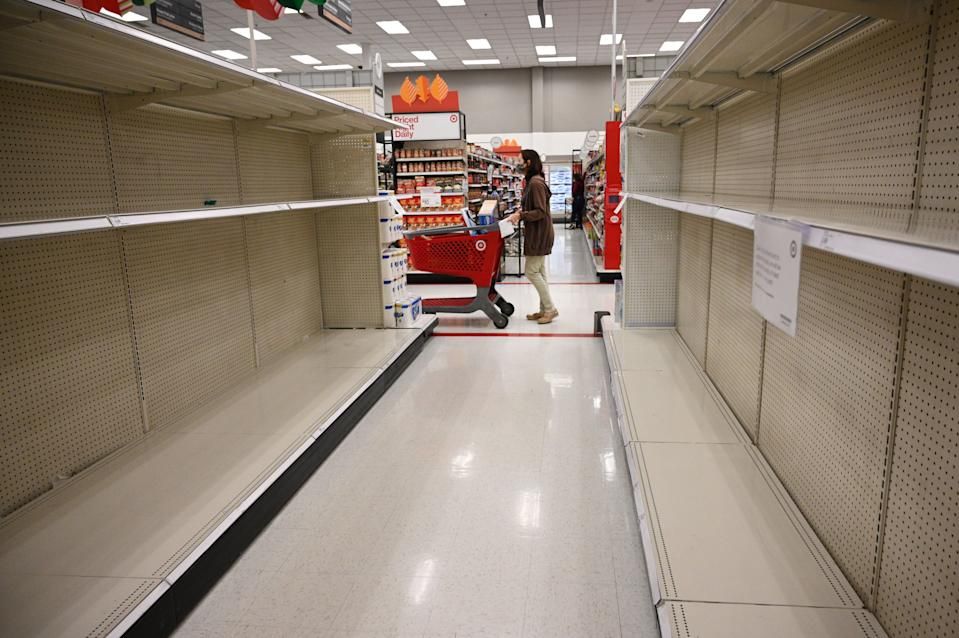 A shopper walks past empty shelves in the paper products aisle of a store in Burbank, California, on November 19, 2020. (Photo by Robyn Beck / AFP)