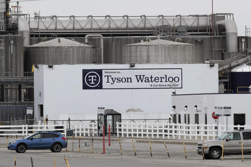 Vehicles sit in a near empty parking lot outside the Tyson Foods plant, Friday, May 1, 2020, in Waterloo, Iowa. (AP Photo/Charlie Neibergall)