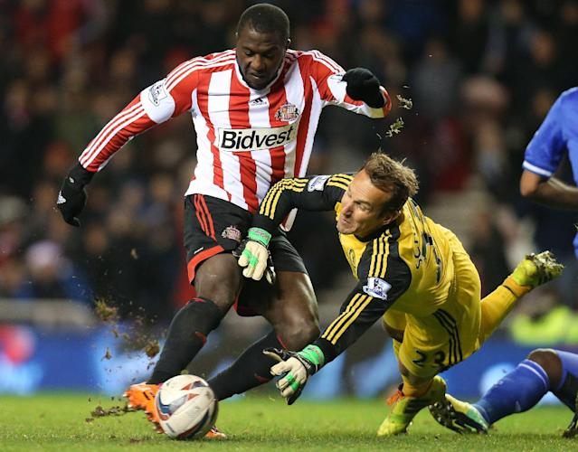 FILE - In this Dec. 17, 2013, file photo, Sunderland's Jozy Altidore, left, hits a shot toward goal past Chelsea's goalkeeper Mark Schwarzer, right, during an English League Cup quarterfinal soccer match in Sunderland, England. Altidore's disappointing first season with Sunderland has less than a month remaining, and it appears as though the American's struggles for playing time aren't finished. Altidore, who scored 31 goals in 41 games for AZ Alkmaar in the Dutch league last year, was an unused substitute for last-place Sunderland in a 2-2 tie with Manchester City on Wednesday, April 16. (AP Photo/Scott Heppell, File)