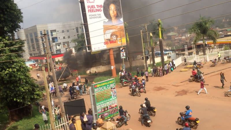 People ride motorcycles as smoke rises from burning objects in a street in Kampala
