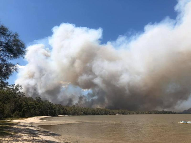 Smoke from Sunshine Coast bushfires as emergency services order the evacuation of several communities.