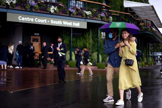 Fans sheltering from rain on day eight at Wimbledon