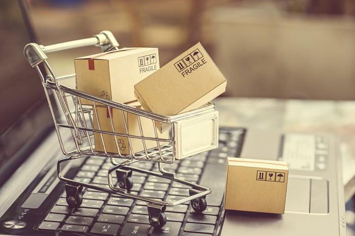 A mini shopping cart full of boxes sitting on a laptop keyboard, illustrating e-commerce.
