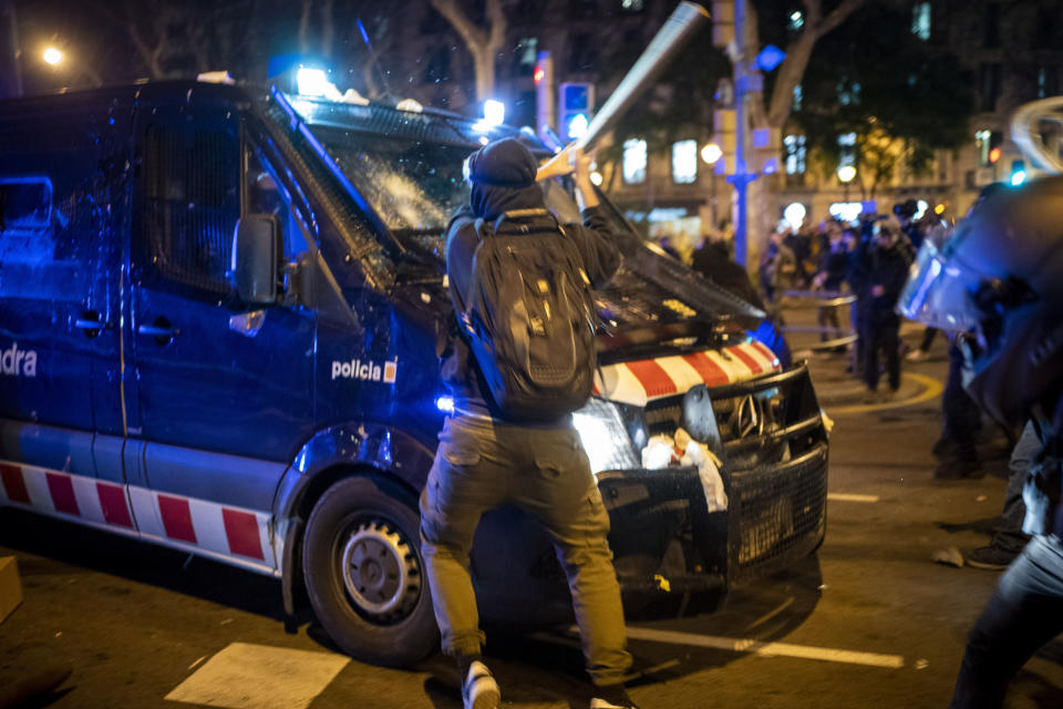 A demonstrator hits a police van with a bat during clashes following a protest condemning the arrest of rap singer Pablo Hasel in Barcelona, Spain, Wednesday, Feb. 17, 2021. The imprisonment of Pablo Hasel for inciting terrorism and refusing to pay a fine after having insulted the country's monarch has triggered a social debate and street protests. (AP Photo/Emilio Morenatti)