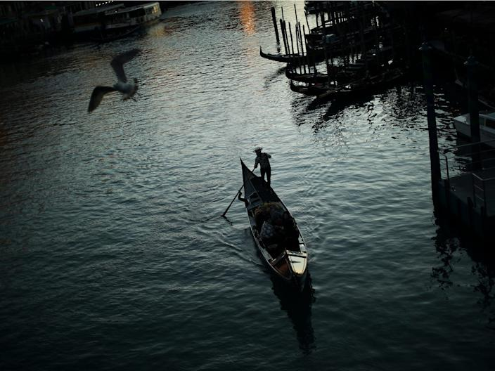 A gondolier on the Grand Canal as the sun sets in Venice, Italy.
