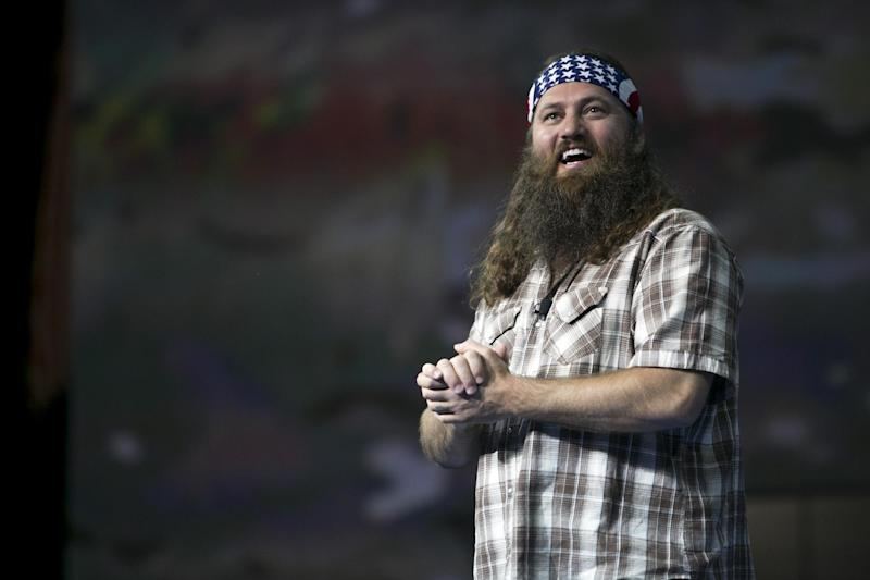 "FILE - Duck Commander CEO and star of the reality television series Duck Dynasty, Willie Robertson speaks to the 6,000 domestic Walmart shareholders at Bud Walton Arena in Fayetteville, Ark., Wednesday, June 5, 2013. Mehgan Cook and Charlie Miller had a camouflage theme as they tied the knot at the new Field & Stream store in Butler County on Saturday morning, Aug. 17, 2013. The two hadn't planned on marrying at the Cranberry Township store, but Cook said they were eager to meet ""Duck Dynasty"" star Willie Robertson. ""I was going to cancel the wedding 'cause I head Willie was coming,"" she said. Instead, Cook said, her mother came up with the idea of a wedding at the store - and they got a surprise when Robertson appeared during the ceremony. (AP Photo/Gareth Patterson)"