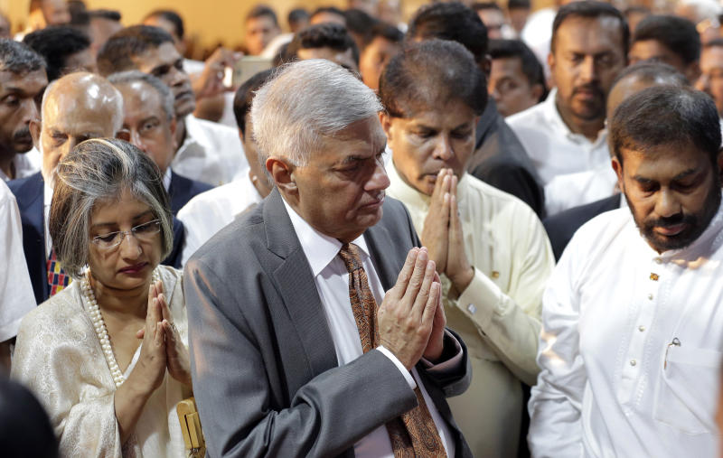 Sri Lanka's reinstated prime minister Ranil Wickeremesinghe, center, greets to Buddhist monks with his wife Maithree, left, after assuming duties in Colombo, Sri Lanka, Sunday, Dec. 16, 2018. Sri Lanka's president has reappointed Ranil Wickremesinghe as prime minister, nearly two months after firing him and setting off weeks of political stalemate. (AP Photo/Eranga Jayawardena)