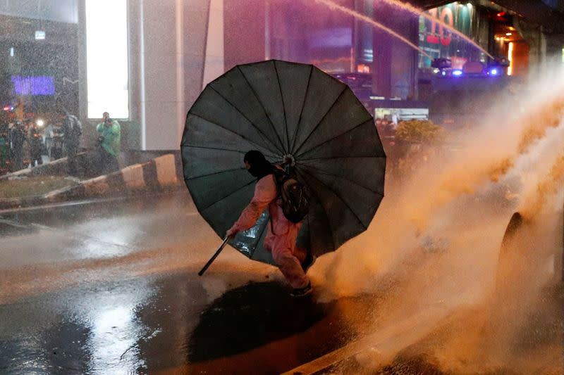 A man takes cover behind an umbrella during an anti-government protest, in Bangkok