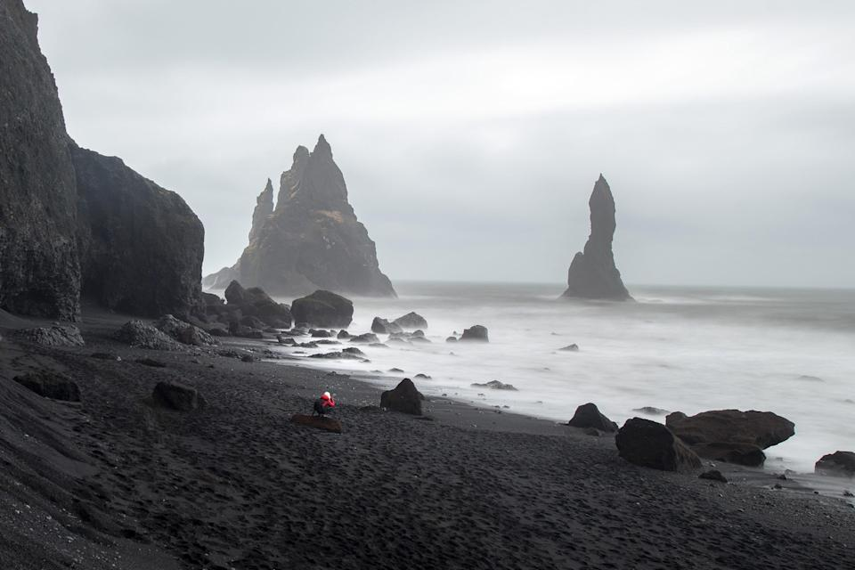 """Just a 20-minute drive from Vik, in southern Iceland, <a href=""""https://www.cntraveler.com/gallery/most-beautiful-black-sand-beaches-in-the-world?mbid=synd_yahoo_rss"""" rel=""""nofollow noopener"""" target=""""_blank"""" data-ylk=""""slk:jet-black sand"""" class=""""link rapid-noclick-resp"""">jet-black sand</a> and spectacularly shaped basalt columns make Reynisfjara one of the most impressive sites in the country. Spend a foggy afternoon strolling along the rugged coast (just strolling—these waters are definitely not made for swimming) and photographing the moon-like rock formations, deep caves, and towering cliff faces."""