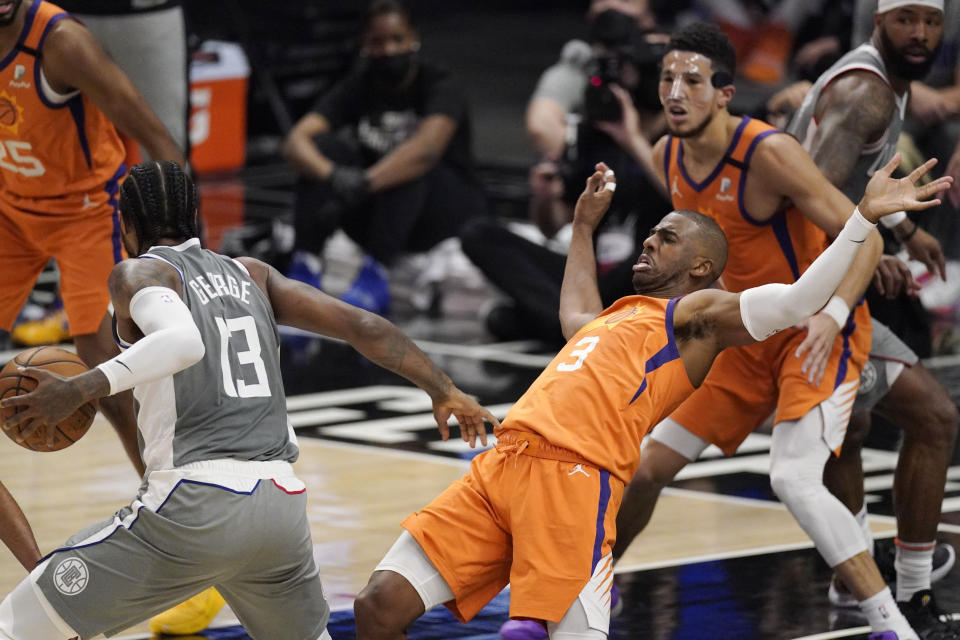 Los Angeles Clippers guard Paul George, left, fouls Phoenix Suns guard Chris Paul during the first half in Game 4 of the NBA basketball Western Conference Finals Saturday, June 26, 2021, in Los Angeles. (AP Photo/Mark J. Terrill)