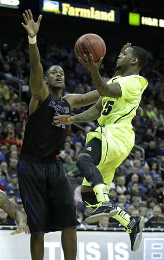 Baylor guard Pierre Jackson (55) puts up a shot under pressure from Kansas State forward Jordan Henriquez (21) during the first half of an NCAA college basketball first round game in the Big 12 Conference tournament, Thursday, March 8, 2012, in Kansas City, Mo. (AP Photo/Charlie Riedel)