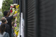 Miami Heat forward Udonis Haslem attaches the flowers he brought to the fence as he pays his respects at a makeshift memorial to the people who were killed and the scores who remain missing, nearly a week after the partial collapse of the Champlain Towers South condo building, Wednesday, June 30, 2021, in Surfside, Fla. (AP Photo/Gerald Herbert)