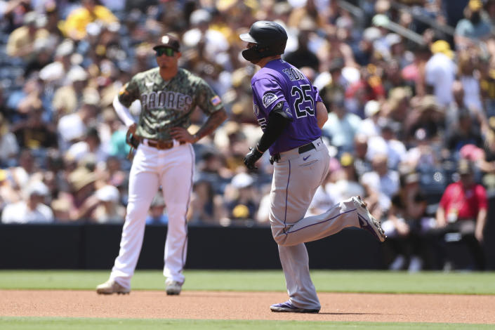 Colorado Rockies' C.J. Cron runs the bases after hitting a solo home run as San Diego Padres third baseman Manny Machado looks on in the fourth inning of a baseball game Sunday, July 11, 2021, in San Diego. (AP Photo/Derrick Tuskan)