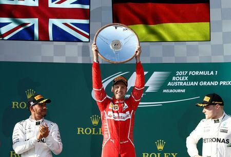 Formula One - F1 - Australian Grand Prix - Melbourne, Australia - 26/03/2017 - Ferrari driver Sebastian Vettel of Germany (C) celebrates alongside Mercedes driver Lewis Hamilton of Britain (L) and team mate Valtteri Bottas of Finland. REUTERS/Brandon Malone