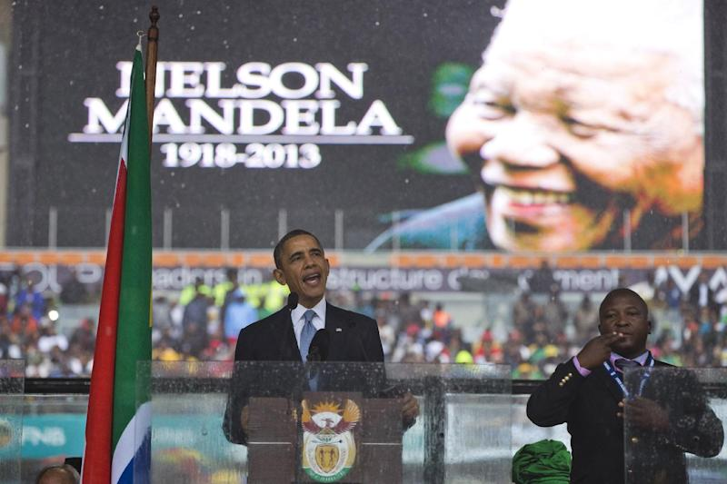 "President Barack Obama delivers his speech next to a sign language interpreter during a memorial service at FNB Stadium in honor of Nelson Mandela on Tuesday, Dec. 10, 2013 in Soweto, near Johannesburg. The national director of the Deaf Federation of South Africa says a man who provided sign language interpretation on stage for Nelson Mandela's memorial service in a soccer stadium was a ""fake.""(AP Photo/ Evan Vucci)"