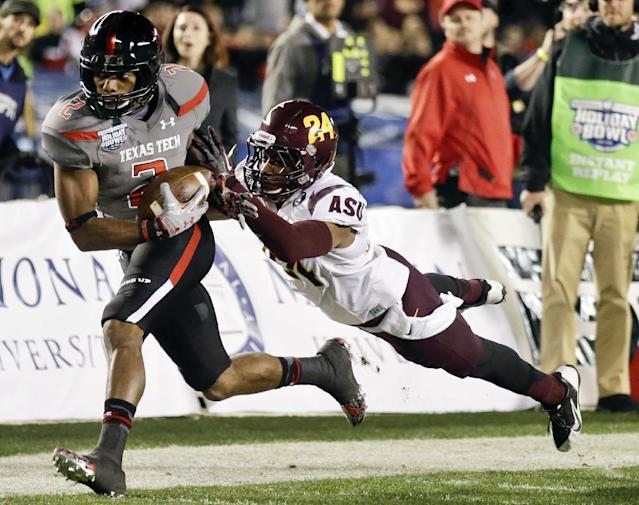 Texas Tech wide receiver Reginald Davis, left, beats Arizona State cornerback Osahon Irabor for a 38-yard pass completion during the first half of the Holiday Bowl NCAA college football game, Monday, Dec. 30, 2013, in San Diego. (AP Photo/Gregory Bull)