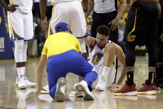 Golden State Warriors guard Klay Thompson is helped off the floor during the first half of Game 1 Thursday night. (AP)