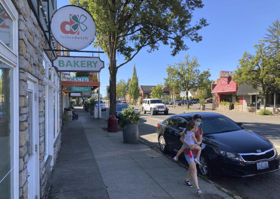 A woman and her child walk through downtown Newberg, Ore., on Tuesday, Sept. 21, 2021. The Chehalem Valley Chamber of Commerce told the school board that it has received numerous phone calls and emails from people saying they will boycott Newberg, the valley's main town, because of its ban on educators displaying Black Lives Matter and gay pride symbols in schools. (AP Photo/Andrew Selsky)